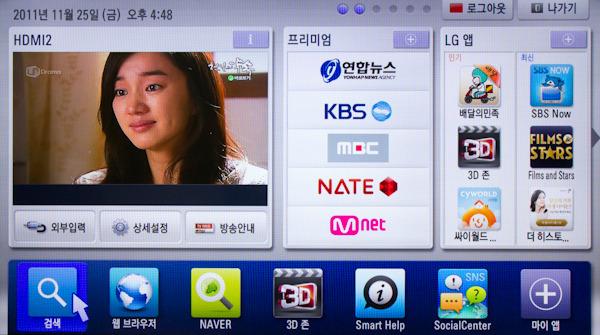 LG 시네마 3D 스마트 TV의 홈 대시보드 화면, 하단에 검색, 웹브라우저 등의 아이콘들이 있다. 마우스포인터는 검색을 향해 있다.