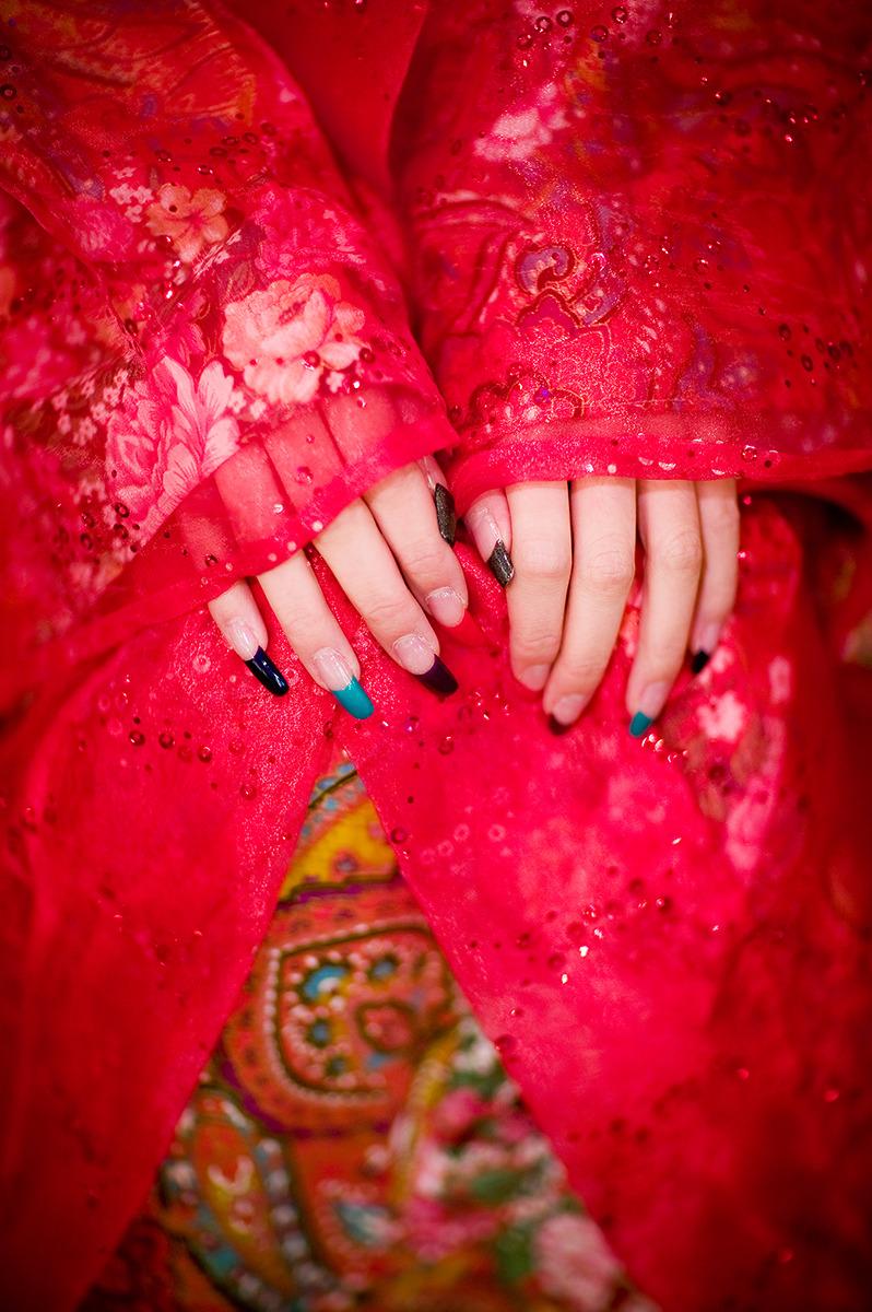 형형색색의 메니큐어를 칠한긴 손톱과 왜색짙은 붉은색 의상을 걸고있는 손