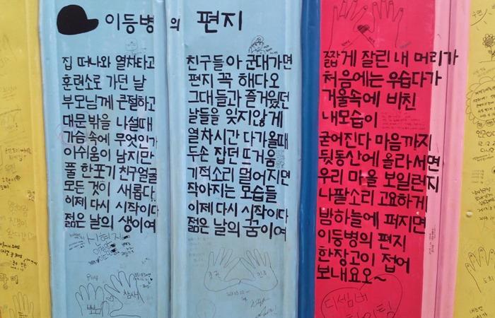 사진: 팬들이 벽에 써 놓은 김광석의 노래 가사. 이등병의 편지 등이 수록된 김광석 노래의 저작권은 집안의 돈싸움으로 이어졌다. 김광석 아내와 친족은 여러 차례의 법정싸움을 벌였다. [사망 후의 김광석 부인]